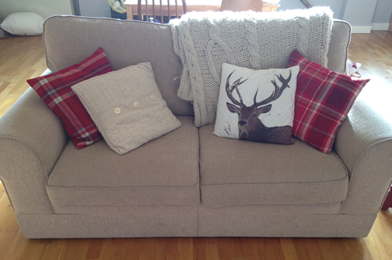 Autumnal sofa with tartan, knitted and stag pillows and a cable knit throw yellow feather blog