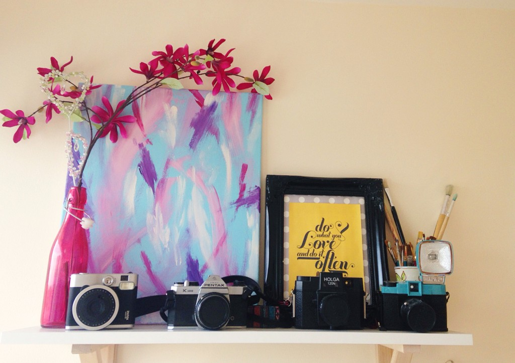 Camera shelf with four cameras, pentax, Holga, Lomo and Instax. with artwork and flowers