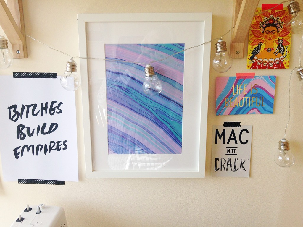 Close up of some of the artwork on the gallery wall, marbled print, bitches build empire quote and other colourful and inspiring postcards