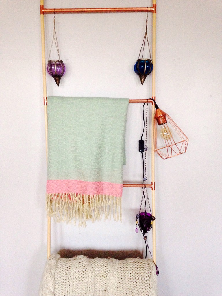 Handmade copper and wood decorative ladder to hold blankets, votives and a copper wire lamp.