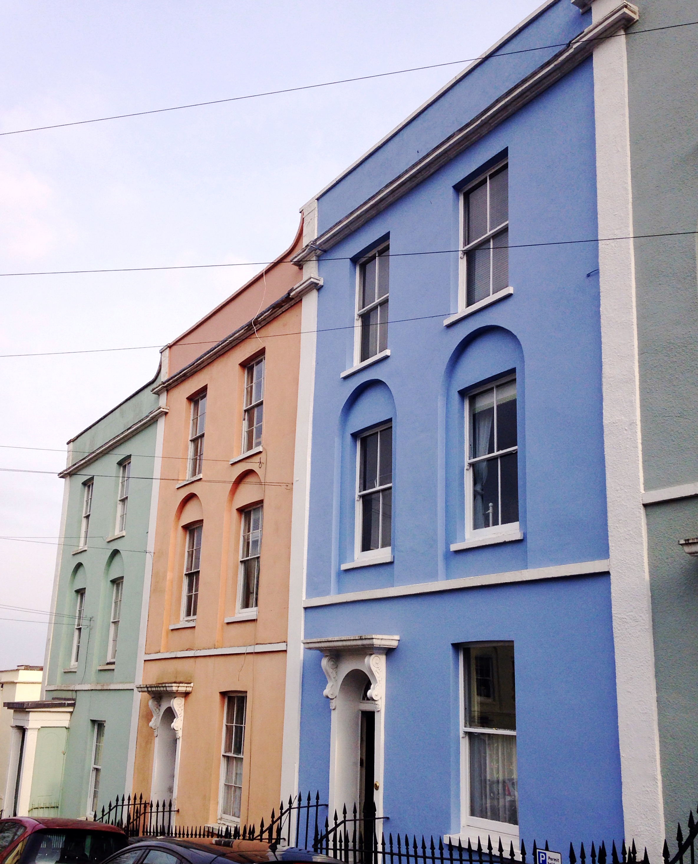 Mint green, coral and blue row of painted houses in Kingsdown Brisol