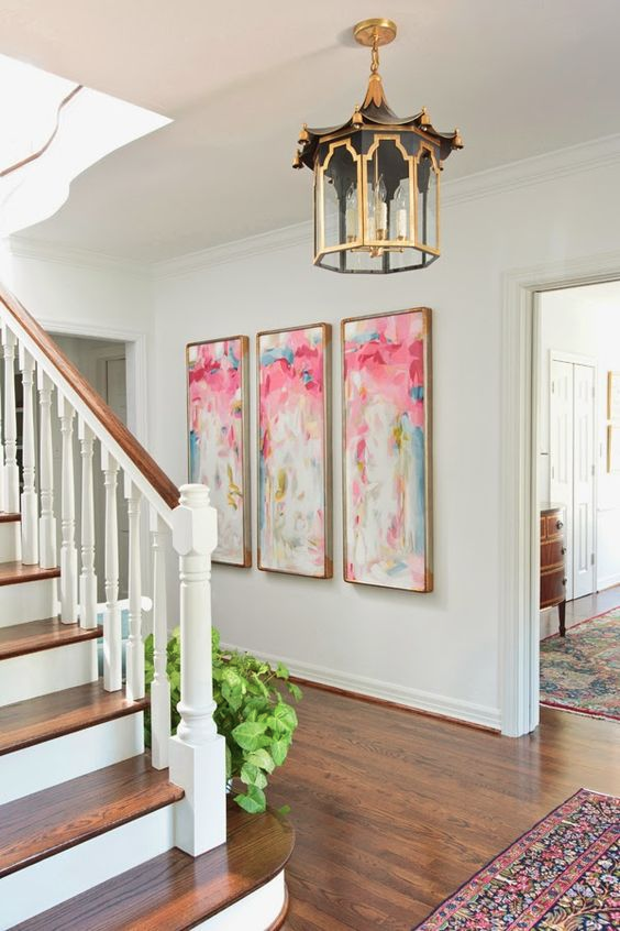 Colourful art hung in a hallway - How to add art to your home