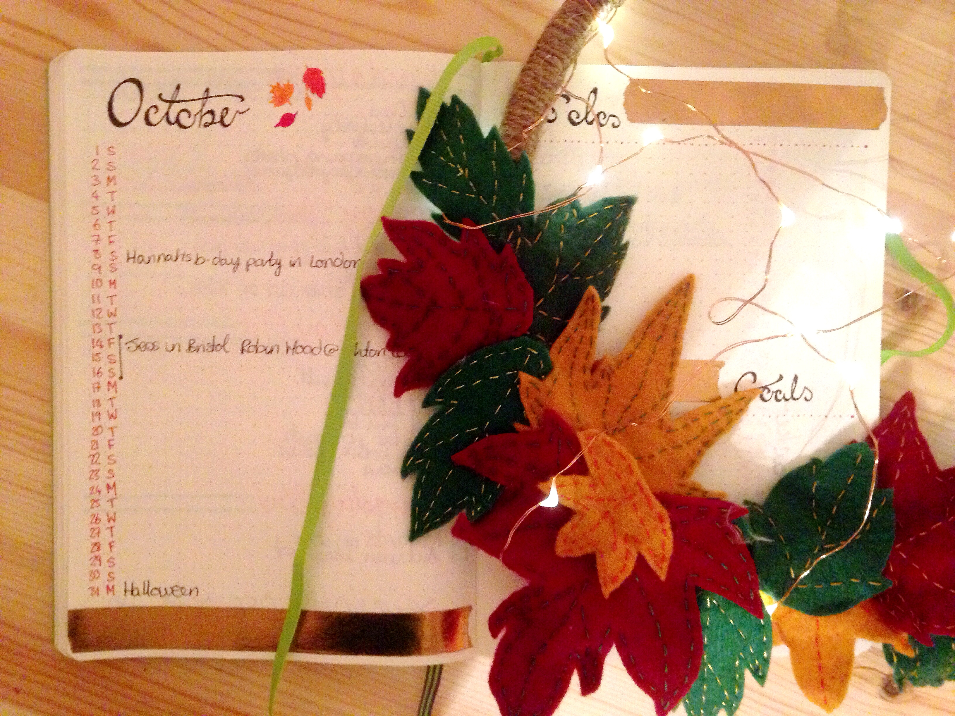 bullet journal autumn update. October's monthly calendar spread with autumnal leaf wreath and fairy lights