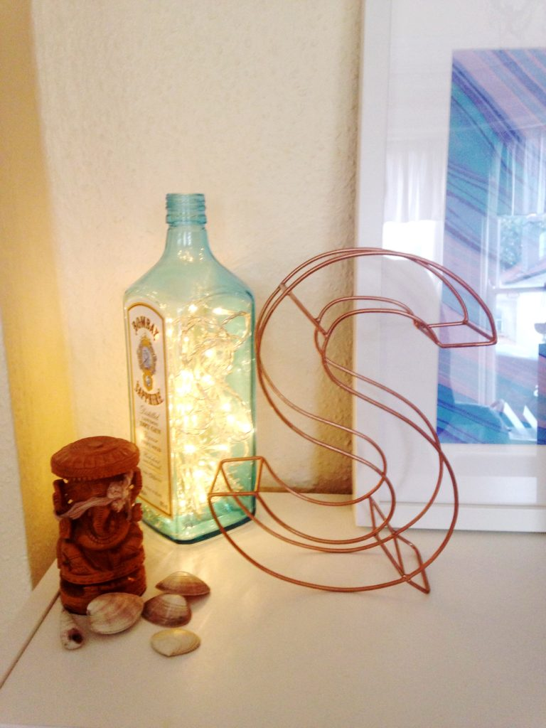 autumnal home decor touches fairy lights in bombay sapphire bottle