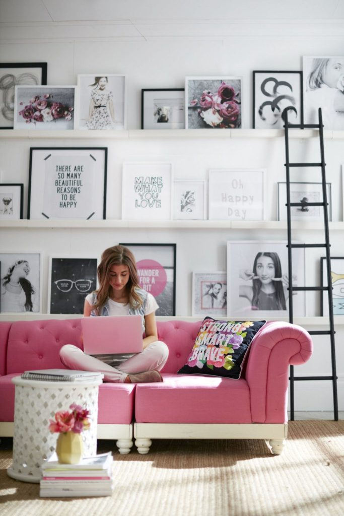 Pink sofa in girly living room with monochrome picture wall