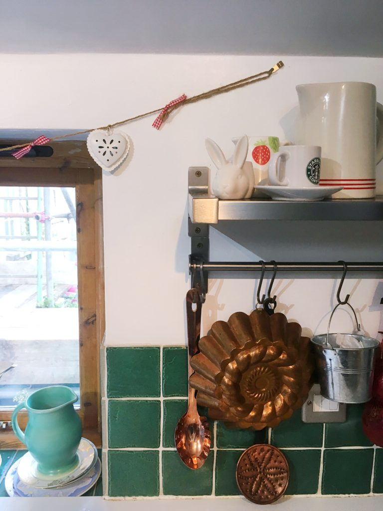Kitchen tour yellow feather blog we hung our copper utensils from this rail to save space