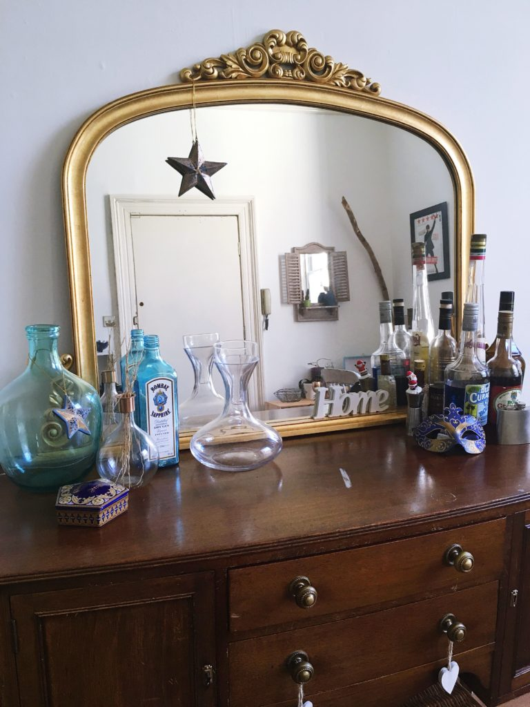 Sideboard with dramatic mirror and barware Living area tour yellow feather blog
