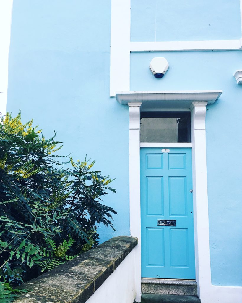 blue painted house with blue door colourful cliftonwood yellow feather blog