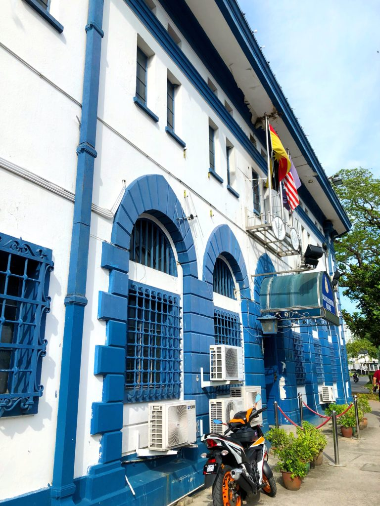 police station blue and white colonial building colourful kuching malaysia yellow feather blog