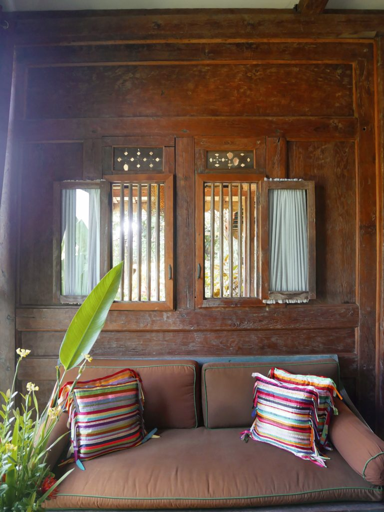 sofa below wooden window living area Rumah Mandau village house accomodation desa seni 1