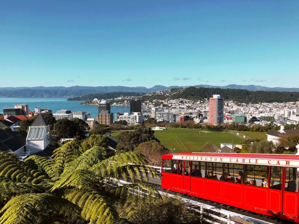 Red cable car going up the hill past Victoria University, view over Wellington  city and bay