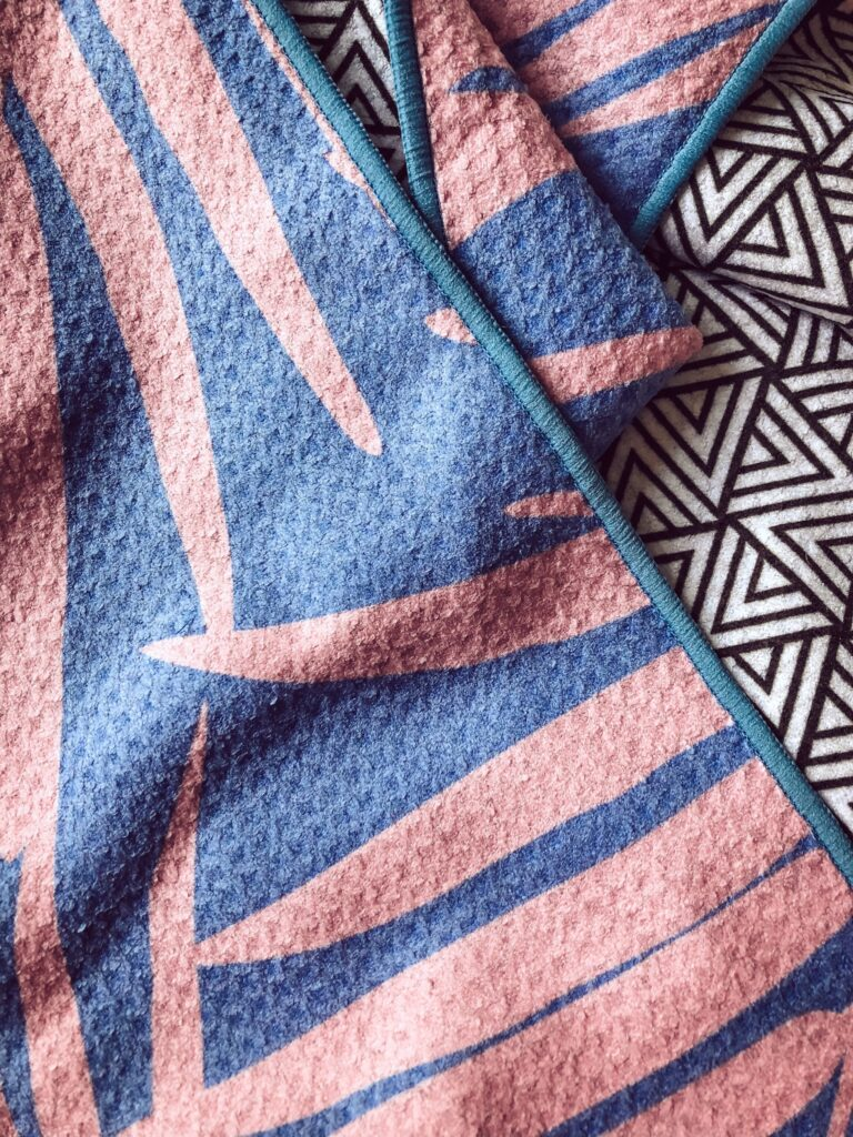 between two palms tesalate beach towel. Pink and blue patterned towel with reverse side showing a geometric white and black triangles print