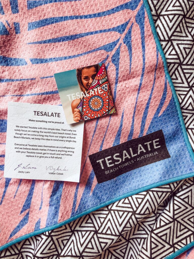 teselate beach towel pink and blue palm printed towel with a black and white triangle geometric print on the reverse